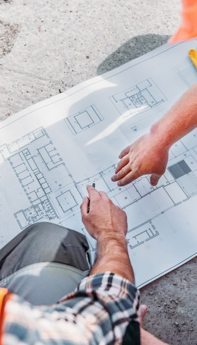 high angle view of builders pointing at blueprint