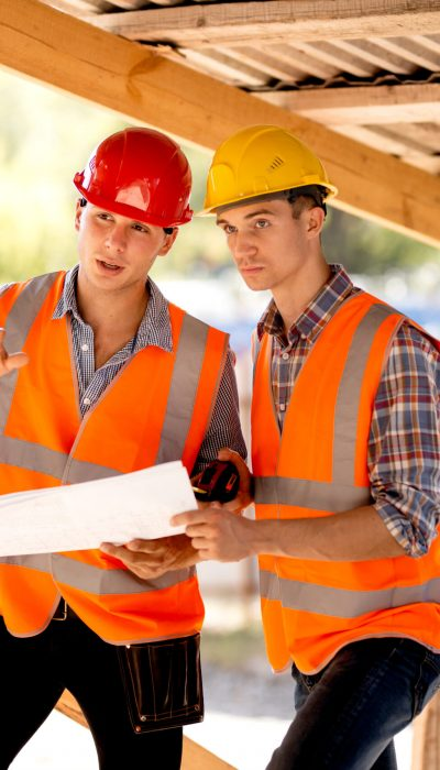 Two men dressed in shirts, orange work vests and helmets explore construction documentation on the building site near the wooden building constructions .